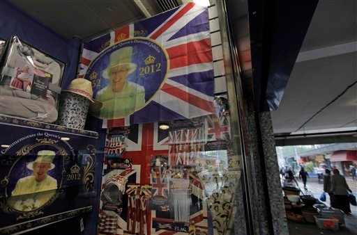 Memorabilia marking Britain's Queen Elizabeth II's upcoming Diamond Jubilee celebrations decorate a shops front window as people walk in a shopping center in east London, Monday, May, 14, 2012. (AP)
