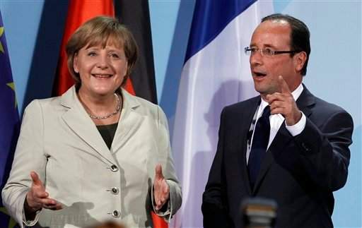 German Chancellor Angela Merkel, left, and the President of France, Francois Hollande, right, gesture after a press conference as part of a meeting at the chancellery in Berlin, Germany, Tuesday, May 15, 2012. (AP Photo/Michael Sohn)