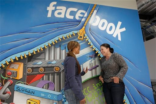 In this Feb. 8, 2012 photo shows two workers inside of Facebook headquarters in Menlo Park, Calif. Facebook stock is expected to begin trading publicly on May 18. (AP Photo/Paul Sakuma)