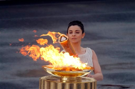 High priestess Ino Menegaki lights the torch with the Olympic Flame, during a handover ceremony for the Olympic flame at Panathenaean stadium in Athens, Thursday, May 17, 2012. (AP Photo/Kostas Tsironis)