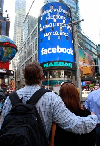 Matts and Maria Nedermam, tourists visiting from Sweden, view Nasdaq's giant monitor as it shows a welcome message for Facebook before the company began trading on the Nasdaq stock market, Friday, May 18, 2012, in New York.