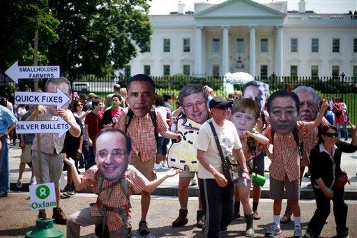 Tourist pose for photographers with Oxfam activist wearing masks depicting G8 world leaders during a demonstration outside the White House in Washington, Thursday, May 17, 2012. (AP)