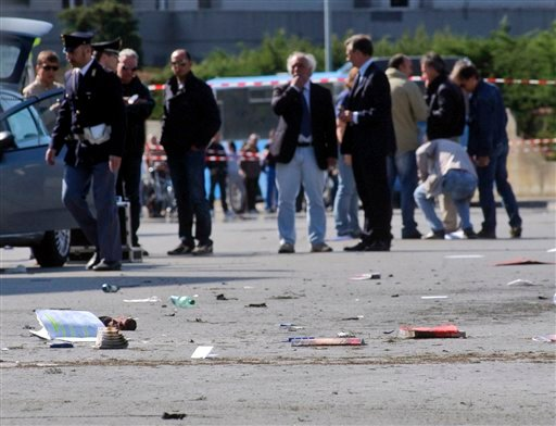 "Italian policemen, background left, walk on the site where an explosive device went off outside ""Francesca Morvillo Falcone"" high school in Brindisi, Italy, Saturday, May 19, 2012. Several students were wounded. (AP Photo/Max Frigione)"
