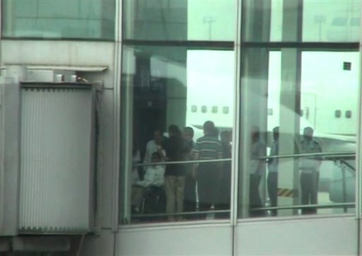 This video image taken from AP video shows blind Chinese activist Chen Guangcheng, left, pushed in a wheelchair from an elevator to a sky bridge that is connected to a plane at Beijing International airport Saturday May 19, 2012. (AP)