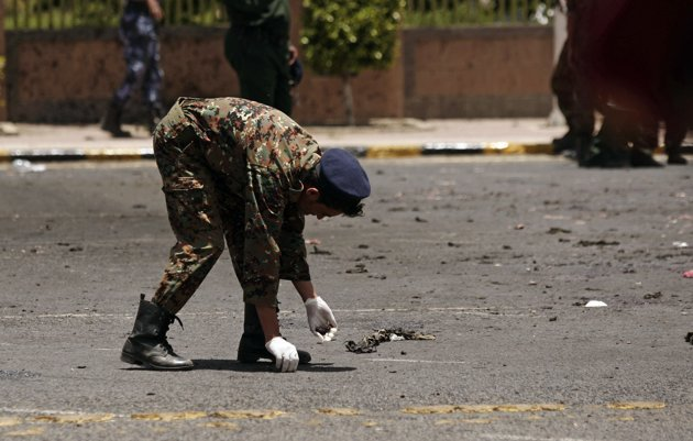A policeman collects evidence at the site of a suicide bomb attack at a parade square in Sanaa, Yemen, Monday, May 21, 2012. Officials say Monday's bombing near Sanaa's presidential palace is one of the deadliest attacks in the city in months. (AP Photo)