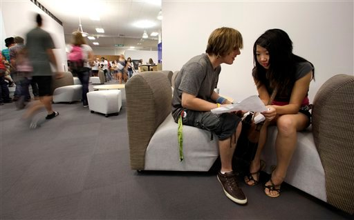 In this Aug. 17, 2011 file photo, seniors Preston Colasanti and Lily Yang compare schedules on the first day of school at a temporary high school in a converted big-box store in Joplin, Mo. (AP)