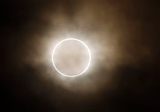 The moon slides across the sun, showing a blazing halo of light, during an annular eclipse at a waterfront park in Yokohama, near Tokyo, Monday, May 21, 2012. (AP Photo/Shuji Kajiyama)
