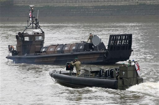 In this Wednesday May 9 2012 picture, a Royal Marines landing craft, top, fitted with an American-made Long Range Acoustic Device (LRAD) at the front, exercises with a patrol craft on the river Thames in London. (AP Photo/Sang Tan)