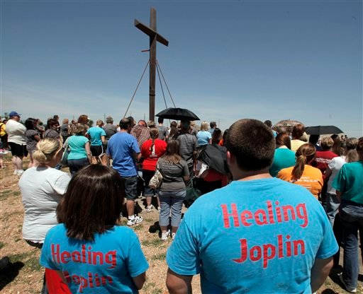 Parishioners gather around the cross at St. Mary's Catholic Church on Tuesday, May 22, 2012, in Joplin, Mo. (AP Photo/Charlie Riedel)