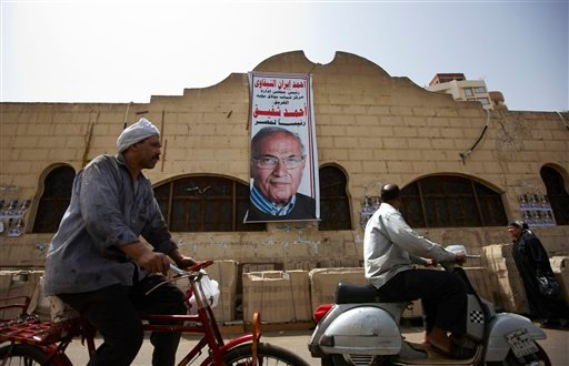 "An Egyptian man rides his bicycle near a poster of presidential candidate Ahmed Shafiq with Arabic writing that reads, ""Ahmed Shafiq, for Egyptian presidency,"" in Cairo, Egypt, Tuesday, May 22, 2012. (AP Photo/Fredrik Persson)"