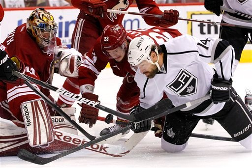 Los Angeles Kings' Justin Williams (14) battles with Phoenix Coyotes' Oliver Ekman-Larsson (23), of Sweden, and goalie Mike Smith, left, for the puck in the second period during Game 5 of the NHL hockey Stanley Cup Western Conference finals May 22, 2012.
