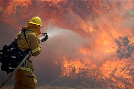 Firefighter Scott Abraham, of the San Bernardino County Fire Department, sprays water as his crew tries to keep the fire from crossing a San Diego County road Friday, May 25, 2012, near Julian, Calif. (AP photo)