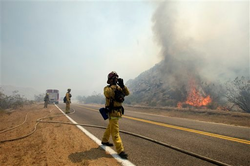 Firefighter Jay Dimoff, of the San Bernardino County Fire Department, yells to his crew as they try to keep fire from crossing a San Diego County road Friday, May 25, 2012, near Julian, Calif. (AP Photo/Gregory Bull)