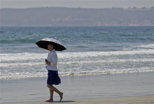 In this May 22, 2012 photo, a woman walks barefoot along the Coronado Beach in Coronado, Calif.
