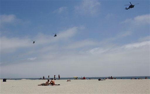 In this May 22, 2012 photo, part of a Navy helicopter squadron flies over beach goers on the Coronado Beach in Coronado, Calif.