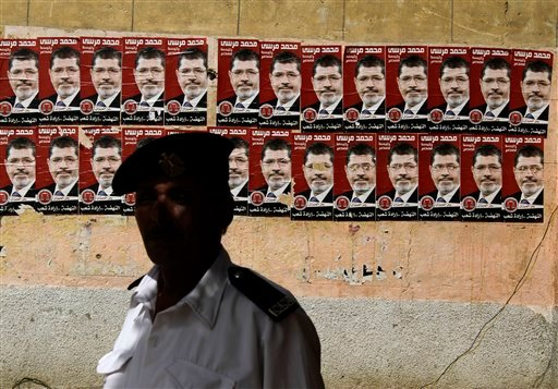 An Egyptian policeman stands by posters of presidential election candidate Mohammed Morsi Thursday, May 24, 2012, outside a polling station in Cairo, Egypt. (AP)