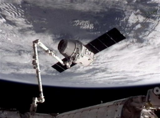 NASA-TV shows the SpaceX Dragon commercial cargo craft, top, after Dragon was grappled by the Canadarm2 robotic arm and connected to the International Space Station May 25, 2012. (AP Photo/NASA)