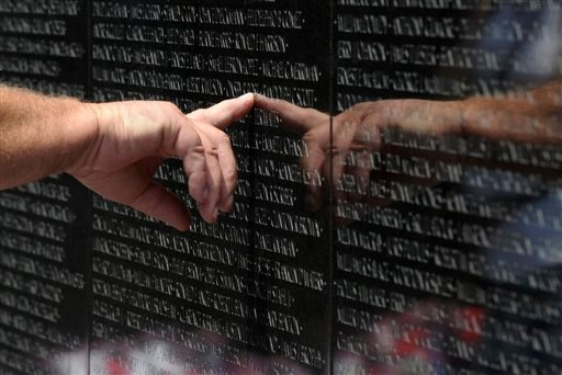 A visitor to the Vietnam Veteran's Memorial touches the name of a fallen soldier etched on the wall of the memorial in Washington, Friday, May 25, 2012. (AP Photo/Susan Walsh)