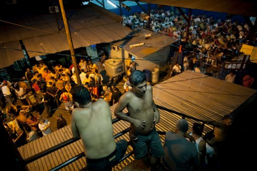 In this May 3, 2012 photo, inmates gather outside their cells in San Pedro Sula Central Corrections Facility in San Pedro Sula, Honduras. (AP Photo/Rodrigo Abd)
