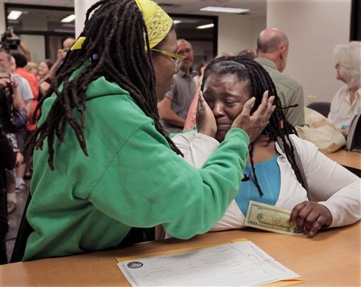 In this June 1, 2011 file photo, Janean Watkins, left, and Lakeesha Harris embrace after being the first in line to obtain a civil union license from the Cook County Office of Vital Records in Chicago.  (AP Photo/M. Spencer Green, File)