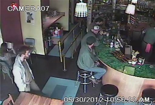 This frame grab provided by the Seattle Police Department shows a man believed to be the suspect in a shooting, left, at Cafe Racer on Wednesday, May 30, 2012 in the University district of Seattle. (AP Photo/Seattle Police Department)