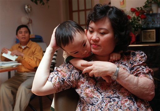In this May 25, 1997 file photo, Phan Thi Kim Phuc holds her son Thomas, 3, in their apartment in Toronto. (AP)
