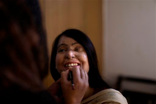 In this Saturday, May 19, 2012 photo, Pakistani acid attack survivor, Naila Farhat, 22, is having makeup applied on her face by nurse Fawziya Hameed, 30, before attending an event, at the Acid Survivors Foundation (ASF), in Islamabad, Pakistan. (AP)