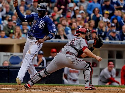 San Diego Padres' Cameron Maybin, left, races past Arizona Diamondbacks catcher Miguel Montero while beating the throw and scoring on a base hit by Yonder Alonso during the fourth inning of a baseball game on Saturday, June 2, 2012. (AP Photo)