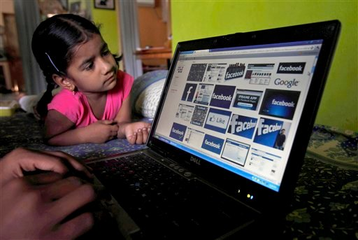 FILE- In this Friday, May 18, 2012, file photo, a child looks at a laptop displaying Facebook logos in Hyderabad, India. Facebook said Monday, June 4, 2012, it is testing out ways to allow younger kids on its site without needing to lie. (AP Photo)