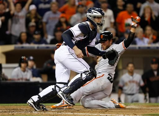 San Diego Padres catcher John Baker moves up the line to corral a wide throw as San Francisco Giants' Brandon Crawford scores the go ahead run in the seventh inning of a baseball game Tuesday, June 5, 2012 in San Diego. (AP Photo/Lenny Ignelzi)