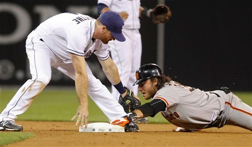 San Francisco Giants' Brandon Crawford hangs onto the base as San Diego Padres second baseman Logan Forsythe applies a late during a steal attempt in the seventh inning of a baseball game Tuesday, June 5, 2012 in San Diego.