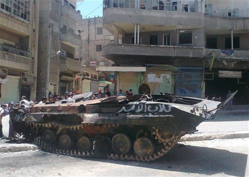 """In this citizen journalism image provided by Edlib News Network ENN, anti-Syrian regime citizens look at a Syrian military tank with Arabic that reads, """"Assads' dogs,"""" that was damaged during clashes between rebels and Syrian government forces. (AP Photo)"""