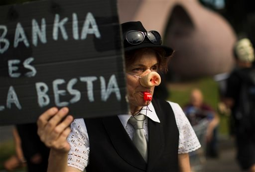 """A demonstrator holds a banner reading in spanish """"Bankia is a wild animal"""" during a demonstration next to a Bankia bank branch in Barcelona, Spain, Saturday June 2, 2012. (AP Photo/Emilio Morenatti)"""