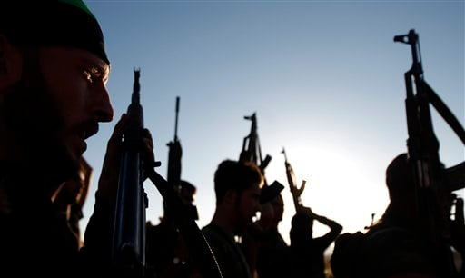 Free Syrian Army members raise their weapons during a training session on the outskirts of Idlib, Syria, Thursday, June 7, 2012. (AP Photo)
