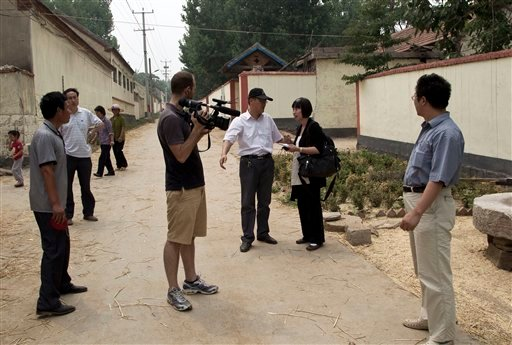 Local officials urge journalists to leave an area near the house where blind activist Chen Guangcheng was under house arrest, at the Dongshigu village, Shandong province, China, Friday, June 8, 2012. (AP Photo/Andy Wong)