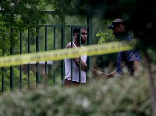 A man, at left, is greeted by an investigator inside a housing complex at the scene of a shooting, Sunday, June 10, 2012, in Auburn, Ala. (AP)