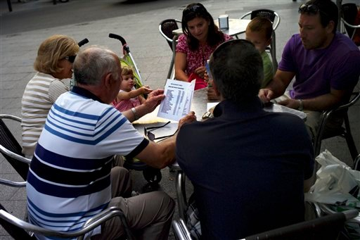 A Spanish family check the prices of tapas on a terrace in downtown Madrid, Saturday June 9, 2012. Spain will ask for a bank bailout from the eurozone, becoming the fourth and largest country to seek help since the single currency bloc's debt crisis erupt