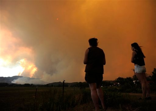 Donna Dundon, left, and Arianna Roupinian, of Fort Collins, Colo., watch a fire burning in a mountainous area about 15 miles west of Fort Collins, on Sunday, June 10, 2012.  (AP Photo/The Denver Post, Helen H. Richardson)