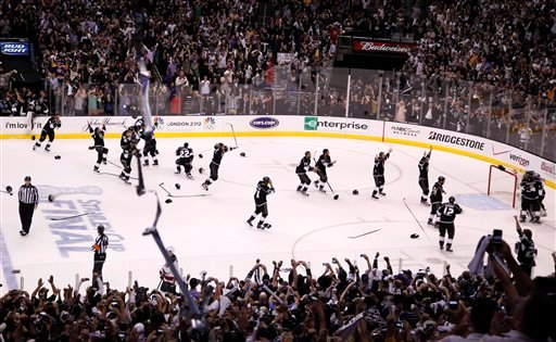 The Los Angeles Kings pour onto the ice to celebrate winning the Stanley Cup.