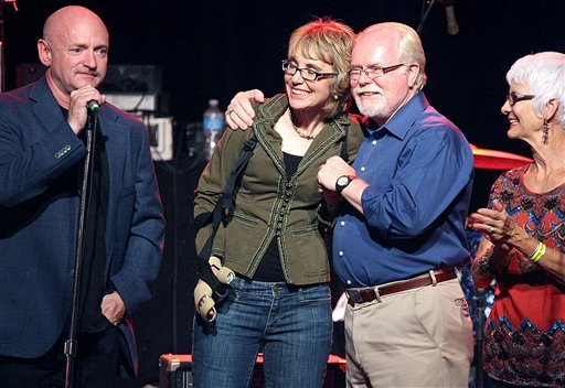 Mark Kelly, from left, former congresswoman Gabrielle Giffords, Ron Barber and Nancy Barber gather during a get-out-the-vote rally at the Rialto Theater in downtown Tucson, Ariz., Saturday, June 9, 2012. (AP Photo/Arizona Daily Star, Mamta Popat)