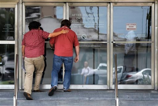 Time-Picayune reporter Ramon Vargas, left, pats the back of movie critic Mike Scott as they walk into the newspaper's offices after learning learning their fate by the company in New Orleans, Tuesday, June 12, 2012. (AP Photo/Gerald Herbert)