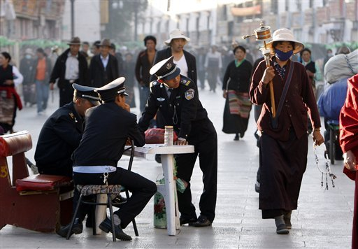In this June 19, 2009 file photo, security guards keep watch over Buddhist pilgrims as they walk on the Barkhor, the circular route around the Jokhang Temple in Lhasa, the capital of Tibet, China. (AP Photo/Greg Baker, File)