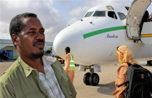In this photo taken Friday, June 8, 2012, Abdikhafar Abubakar prepares to board a plane back to Minneapolis after returning to Mogadishu to visit his mother for the first time in decades, at the airport in Mogadishu, Somalia. (AP Photo/Jason Straziuso)