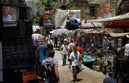 Campaign posters supporting Egyptian presidential candidate Ahmed Shafiq, the last prime minister of deposed president Hosni Mubarak, hang above a popular market in Cairo, Egypt, Tuesday, June 12, 2012. (AP Photo/Amr Nabil)