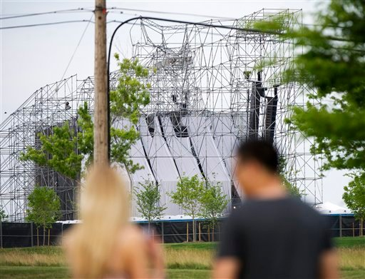People look at a collapsed stage at Downsview Park in Toronto on Saturday, June 16, 2012. Toronto paramedics say one person is dead and another is seriously hurt after the stage collapsed while setting up for a Radiohead concert.