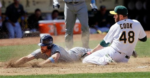 San Diego Padres' Logan Forsythe, left, scores on a wild pitch by Oakland Athletics pitcher Ryan Cook (48) during the ninth inning of a baseball game in Oakland, Calif., Sunday, June 17, 2012. (AP Photo/Jeff Chiu)