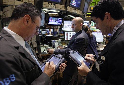 Specialist Meric Greenbaum, center, wotks at his post on the floor of the New York Stock Exchange Monday, June 18, 2012. (AP Photo/Richard Drew)