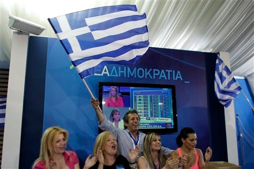 Supporters of the New Democracy conservative party celebrate at an election kiosk at Syntagma square in Athens, Sunday, June 17, 2012. (AP Photo/Kostas Tsironis)