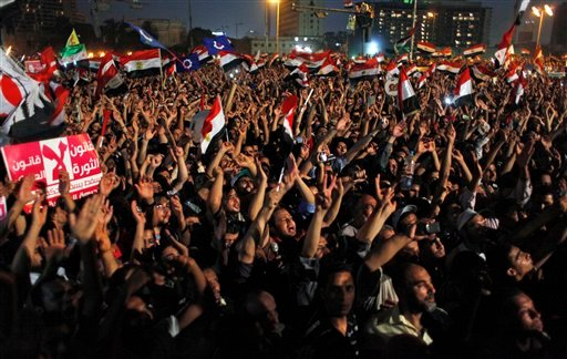 "Egyptian Muslim Brotherhood supporters wave national flags and chant slogans, and one carries a banner that reads in Arabic ""The law of the revolution not the law military,"" during an anti-ruling military council demonstration in Tahrir Square, Egypt."