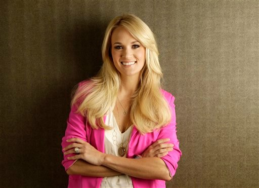 """FILE - This April 19, 2012 file photo shows Carrie Underwood in Nashville, Tenn. Underwood's latest hit """"Good Girl"""" and her """"Remind Me"""" collaboration with Brad Paisley are up for video of the year for the 2012 CMT Awards, which kick off at 8 p.m. EDT"""